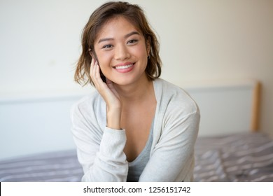 Portrait of cheerful young woman sitting on bed. Asian girl looking at camera and smiling indoors. Beauty concept