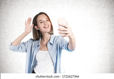Portrait of cheerful young woman in smart casual clothes making video call or selfie and waving to the camera near concrete wall. Concept of communication and social media. Mock up