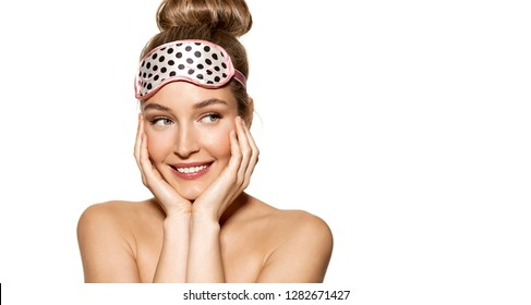 Portrait of cheerful young woman smiling and standing in cute sleeping mask. Bedtime and beauty concept. Lovely model with pretty eyes on white background