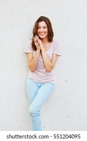 Portrait of cheerful young woman smiling against white wall
