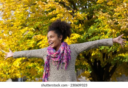 Portrait of a cheerful young woman standing outdoors with arms outstretched