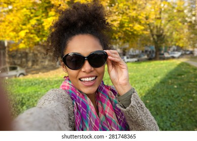 Portrait of a cheerful young woman taking selfie outside
