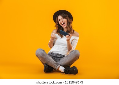 Portrait of a cheerful young woman wearing white shirt and hat sitting isolated over yellow background, texting on mobile phone