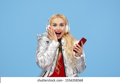 Portrait of cheerful young woman wearing casual silver jacket isolated over blue background, listening to music with headphones, dancing. Wow and surprised face