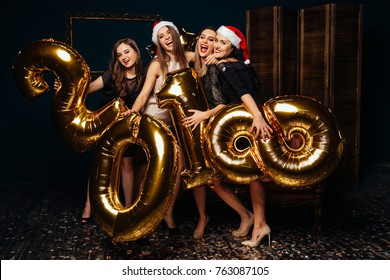 Portrait of cheerful young women in Santa hats at New year party