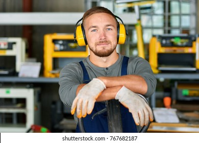 Portrait of cheerful young worker wearing protective headphones posing looking at camera and enjoying work at modern factory