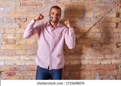 Portrait of a cheering handsome young man in a pink shirt.