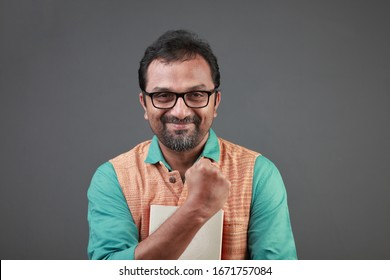 Portrait of a cheering man of Indian ethnicity holding books