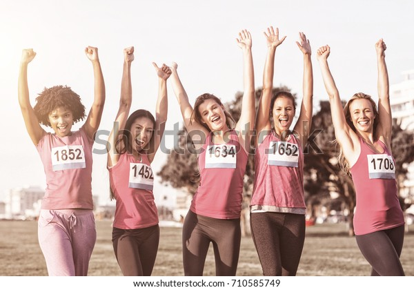 Portrait of cheering women supporting breast cancer marathon in parkland