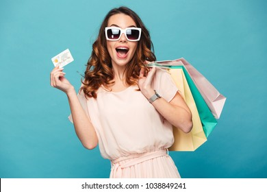 Portrait of a cheery beautiful girl wearing dress and sunglasses holding shopping bags and showing credit card isolated over blue background