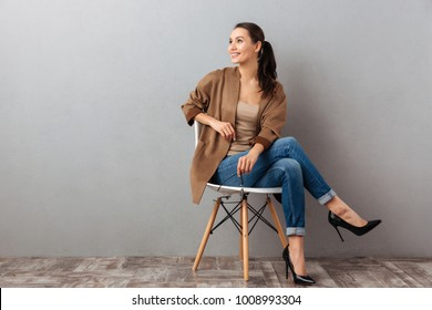 Portrait of a cheery casual asian woman sitting on a chair and looking away at copy space over gray background