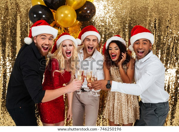 Portrait of a cheery happy multiracial group of friends celebrating New Year together while toasting with champagne glasses isolated over golden shiny background