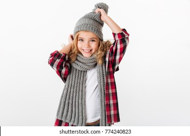 Portrait of a cheery little girl dressed in winter hat and scarf posing and looking at camera isolated over white background