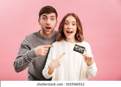 Portrait of a cheery loving couple dressed in sweaters holding credit card and pointing finger isolated over pink background