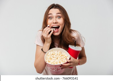 Portrait of a cheery pretty girl holding plastic cup and eating popcorn isolated over white background