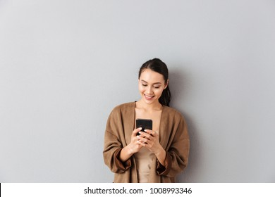 Portrait of a cheery young asian woman using mobile phone while standing over gray background