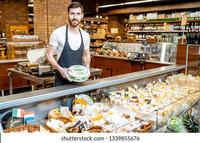 Portrait of a cheese seller in uniform standing with cheese head in the supermarket