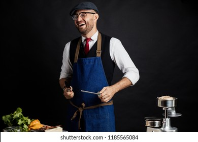 Portrait of chef cook in elegant uniform wearing cap and apron sharpens knife at the restaurant kitchen table over yellow background. Small business, Service and Catering Concept