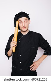 Portrait of chef cook in uniform at the restaurant kitchen.holding a rolling pin