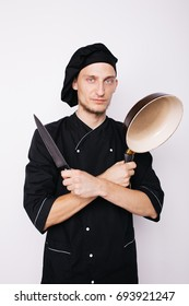 Portrait of chef cook in uniform at the restaurant kitchen.holding a pan and a knife
