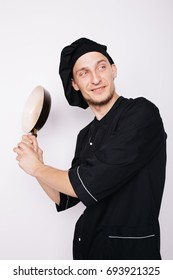 Portrait of chef cook in uniform at the restaurant kitchen.holding a frying pan