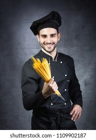 Portrait of a chef cooker in black uniform with spaghetti in his hand, gray background