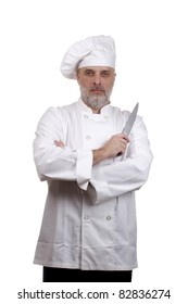 Portrait of a chef with crossed arms and a knife in a chef's hat and uniform isolated on a white background.