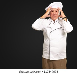 Portrait Of A Chef Having Headache Isolated On Black Background
