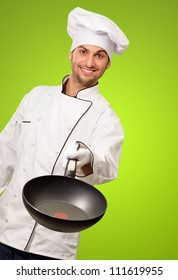 Portrait Of A Chef Holding A Pan On Green Background