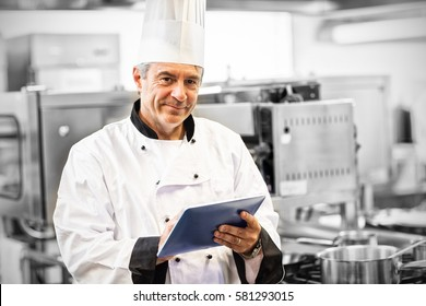 Portrait of chef using his digital tablet in professional kitchen