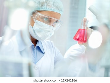 Portrait of a chemist holding a tube with liquid