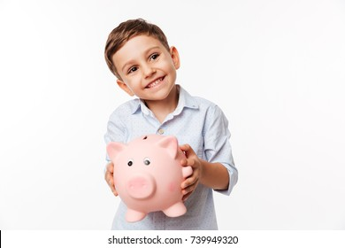 Portrait of a cherry cute little kid holding piggy bank and looking away at copy space isolated over white background