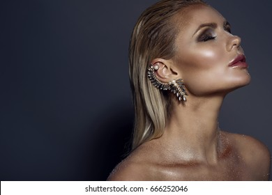 Portrait of chic gorgeous blond woman with wet hair, artistic glittering make-up and the cuff on her ear posing with closed eyes. Isolated on grey background. Copy-space. Jewellery concept. Close up