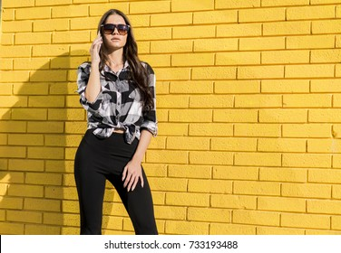 Portrait of a chic woman using mobile phone  in front of a yellow wall