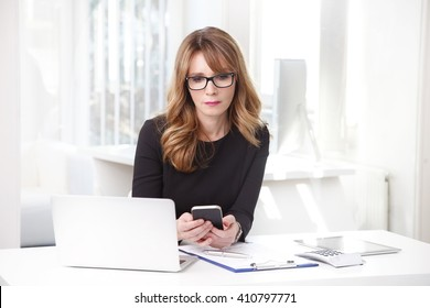 Portrait of a chief financial officer businesswoman using her mobile phone while sitting at office in front of laptop and working.