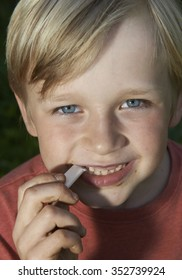 Portrait of child blond Boy Stretching Bubble Gum from Mouth