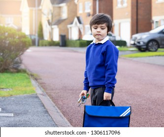 Portrait of Child with bored face holding plastic toy and carrying bag waiting for school bus, Unhappy Pupil of primary school looking down with sad face standing alone on the road, Kid back to school