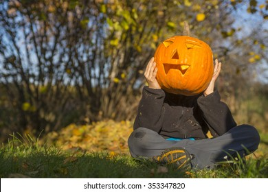 Portrait of child Boy with halloween pumpkin jack-o-lanterns in front of face, sitting on the grass, autumn garden, sunny day