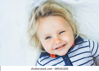 Portrait of a child boy in nature. Smiling happy blond child