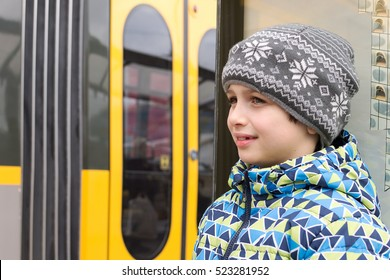 Portrait of a child boy waiting at a public transport stop, bus or tram train in the background,