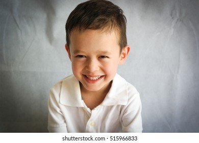 Portrait of a child boy in a white polo shirt on a white background smiling looking at the camera