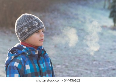 Portrait of a child boy,with vapor coming from his mouth, in a park on  a cold frosty morning .