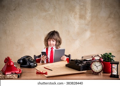 Portrait of child businessman in office. Kid holding gadgets. Communication in business concept