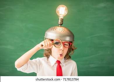 Portrait of child in classroom. Kid with toy virtual reality headset in class. Success, idea and innovation technology concept. Back to school