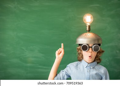 Portrait of child in classroom. Child with toy virtual reality headset in class. Success, idea and innovation technology concept. Back to school. Kid against blackboard with copy space