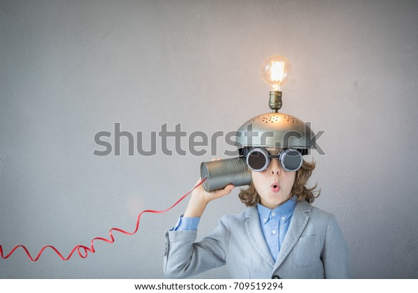 Portrait of child in classroom. Child with toy virtual reality headset in class. Funny kid with light bulb. Communication, idea and innovation technology concept. Back to school