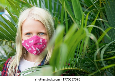 Portrait of child in funny protective mask. New rules to wear cloth face covering at public places. Cancelled cruise, tour due coronavirus COVID 19. Family vacation, travel lifestyle at summer 2020