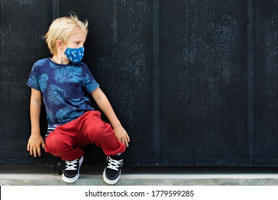Portrait of child in funny protective mask. New rules to keep social distancing, wear face covering at public places. Cancelled cruise, tour due coronavirus COVID 19. Family lifestyle at summer 2020.