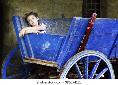 Portrait of a child girl in a blue wooden cart