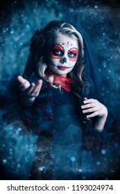 Portrait of a child girl in a costume of Calavera Catrina over dark grunge background. Little girl with sugar skull makeup. Halloween party. Dia de los muertos. Day of The Dead.